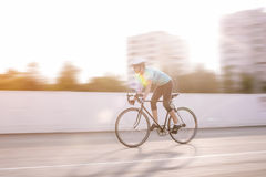 Young female athlete racing on a bike. motion blurred image Stock Photo