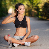 Young female athlete resting after Jogging in a Park Stock Images