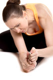 Young female athlete rubbing sore foot. Young athlete girl in sportswear touching aching foot, injured after sport practice, feeling pain in ligament, focus on Stock Image