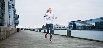 Young female athlete running along the river. Young female athlete running on boardwalk along the river. Fit young woman jogging along the waterfront Royalty Free Stock Photography