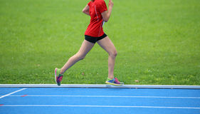 young female athlete running on the color athletics track gblu Stock Photography