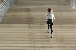 Young female athlete running up stairs Stock Photos