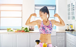 Young female athlete showing biceps at kitchen. Young smiling sportive woman in sportswear showing biceps while standing in light kitchen stock photo