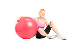 A young female athlete sitting on a floor next to a pilates ball Royalty Free Stock Images