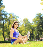 Young female athlete sitting on a grass and holding a bottle, in Stock Photography