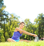 Young female athlete sitting on a mat and stretching in a park Stock Photos