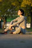 Young female athlete sitting outdoors. And resting after workout Stock Image