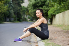 Young female athlete sitting outdoors resting after workout Stock Image
