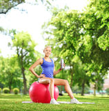 Young female athlete sitting on pilates ball holding a bottle in Stock Photo
