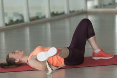 Young female athlete in sports clothes doing warm-up on the rug in the gym with tape royalty free stock photo