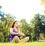 Young female athlete in sportswear doing yoga exercise seated on Stock Photography