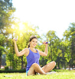 Young female athlete in sportswear exercising with dumbbells in Stock Photography