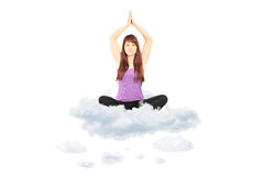 Young female athlete in sportswear sitting on clouds and meditat Royalty Free Stock Image