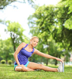 Young female athlete stretching her leg in a park Stock Photo