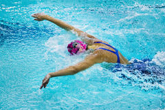Young female athlete swimming butterfly stroke in pool. closeup side view. Chelyabinsk, Russia - October 21, 2015: young female athlete swimming butterfly stroke Royalty Free Stock Image