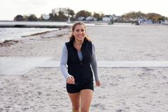 Young female athlete walking on beach smiling Royalty Free Stock Photos