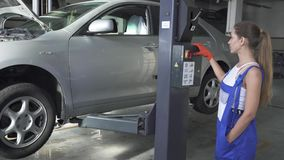 Female young automaster presses a button on a jacking lifting transport mechanism to lower the car up. Car service stock video