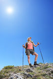 A young female with backpack and hiking poles posing at sunny day Stock Photo