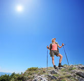 Young female with hiking poles posing at sunny day in mountain Royalty Free Stock Image