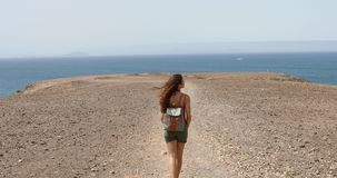 Young female backpacker enjoying ocean breeze and looking Fuerteventura Island in front of her. Hiker traveler girl walking. Young female backpacker enjoying stock video