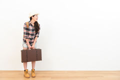 Young female backpacker holding retro suitcase. Cheerful young female backpacker holding retro suitcase standing on wooden floor with white wall background and Stock Image