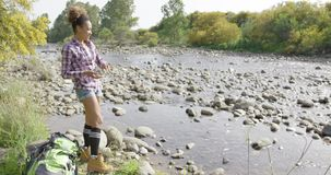 Young female backpacker throwing stones in river stock footage