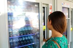 Young female backpacker tourist choosing a snack or drink at vending machine in Venice, Italy. Vending machine with girl. stock photo