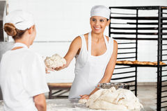Young Female Baker Giving Dough To Colleague. Smiling young female baker giving dough to colleague in bakery royalty free stock photography