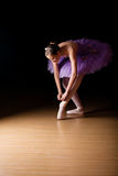 Young female ballerina adjusting her shoes. Young female ballerina wearing a lilac colored tut adjusting her shoes against black background Royalty Free Stock Photos