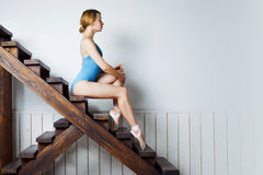 Young female ballet dancer in the blue suit sitting on stairs Stock Image