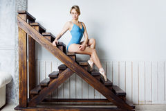 Young female ballet dancer in the blue suit sitting on stairs Royalty Free Stock Photography