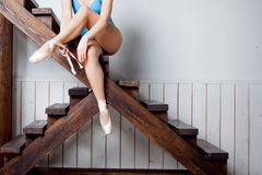 Young female ballet dancer in the blue suit sitting on stairs Royalty Free Stock Image