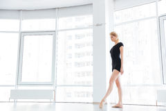Young female ballet dancer is smiling and standing in pose Stock Photography