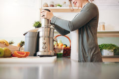 Young female bar employee making fruit juice Royalty Free Stock Photos