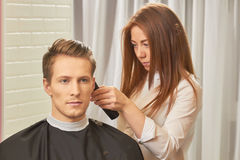 Young female barber at work. Royalty Free Stock Image