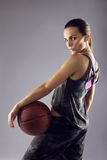 Young female basketball player posing on grey background Royalty Free Stock Photography
