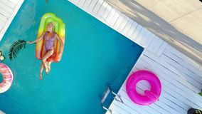 Top view young woman in swimsuit swims in pool on air mattress. Young female basking in sun while swimming in pool on an air mattress, drone shot stock video