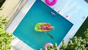 Young female basking in sun while swimming in pool on an air mattress, top view. Young female basking in sun while swimming in pool on an air mattress, drone stock video