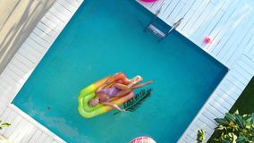 Young female basking in sun while swimming in pool on an air mattress, top view. Young female basking in sun while swimming in pool on an air mattress, drone stock video footage