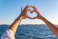 Young female beautiful hands on the background of the sea show the symbol of the heart. Vacation - concept. Young female beautiful hands on the background of royalty free stock photography