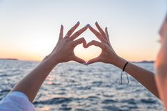 Young female beautiful hands on the background of the sea show the symbol of the heart. Vacation - concept. Young female beautiful hands on the background of royalty free stock image