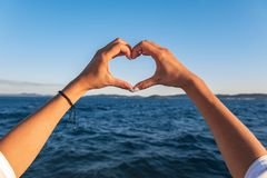 Young female beautiful hands on the background of the sea show the symbol of the heart. Vacation - concept. Young female beautiful hands on the background of stock images