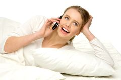 Young female in bed with a mobile phone Stock Image