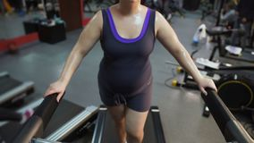 Young female with big belly exercising on treadmill, working hard to lose weight. Stock footage stock video