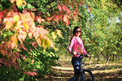 Young female on a bike in autumn Stock Photo