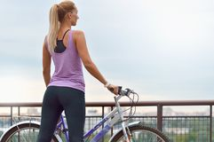 Young female biker next to her bike looking at the city Royalty Free Stock Images