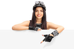 Young female biker ponting on a signboard Stock Photos