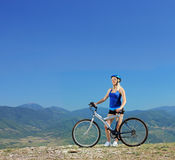 Young female biker posing with a mountain bike outdoors Royalty Free Stock Photography