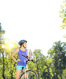 Young female biker posing on a mountain bike on sunny day Royalty Free Stock Image