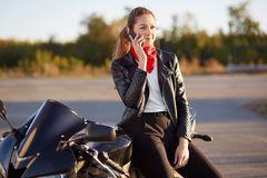 Young female biker with serious expression, has phone conversation via cellular, wears red bandana and leather jacket, poses on mo stock image